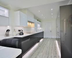 two tone handless acrylic kitchen with ample lighting to make a