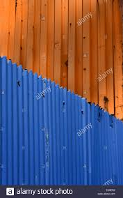 blue corrugated iron fence with orange shipping container stock