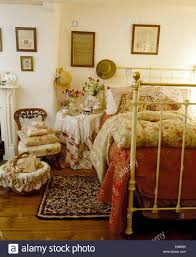 cottage bedroom with floral quilt on white wrought iron bed and