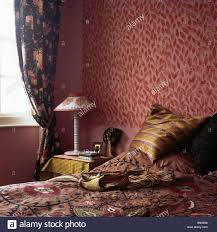patterned red wallpaper in small bedroom with dark blue curtains