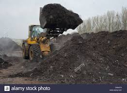 volvo loader turning green compost waste for aeration at municipal