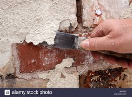house maintenance man scraping off flaking paint on old brickwork