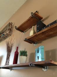 industrial floating shelves use rough cedar planks and plumbing