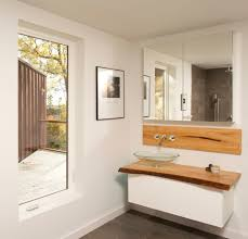 white wooden vanity with brown wooden top and glass bowl sink also