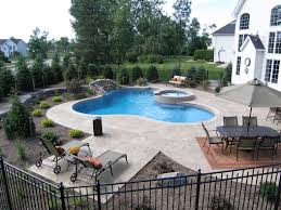 gunite pool with a spill over spa water falls and outdoor kitchen