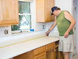 carpenter installing cabinets and counter top in a kitchen stock