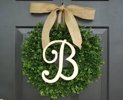 decorating round preserved boxwood wreath with cool ribbon for