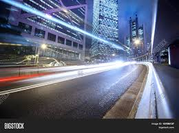 fast moving cars lights blurred over modern city background stock