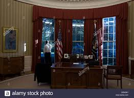 us president barack obama looks out the window of the oval office