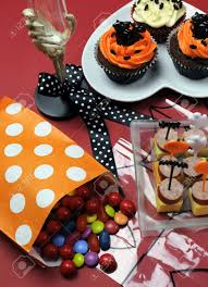 happy halloween party table with skeleton glass cupcakes candy
