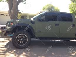 Ford Raptor Green - photo of a matte olive green ford raptor with custom wheels shocks