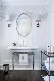 oval beaded mirror over 2 leg washstand transitional bathroom