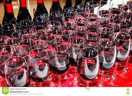 glasses and bottles of red wine on cocktail party table stock