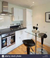Bar Stools At Glass Topped Breakfast Table In Kitchen Of Apartment - Breakfast table in kitchen