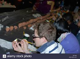 people painting small clay pots for candles at a community