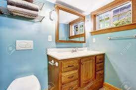 blue bathroom interior with wooden vanity cabinet and wood window