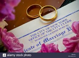 new york wedding band marriage certificate on desk with two gold wedding rings city