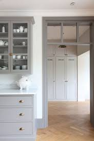 gray kitchen cabinets brass hardware herringbone floor