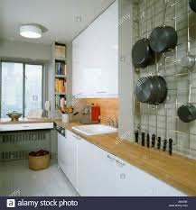 White Galley Kitchens Saucepans Stored On Wire Wall Rack In Modern White Galley Kitchen