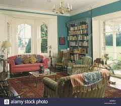colourful cushions and throws on sofas in blue livingroom with