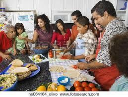stock photo of large hispanic family in kitchen preparing food
