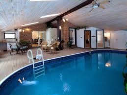 luxurious indoor pool with an attached sauna and shower area view