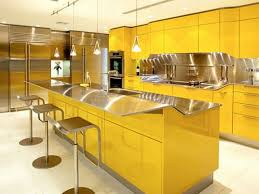 yellow wooden kitchen cabinet and island with silver countertop