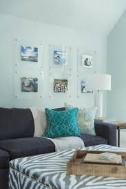 clear acrylic picture frames over dark gray linen sofa