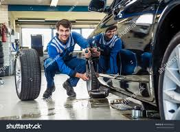 full length confident male mechanic crouching stock photo