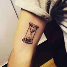 small hourglass on right inner arm