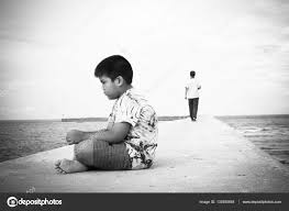 little boy unhappy sitting alone on bridge black and white tone