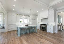white cabinets with powder blue kitchen island and sawn oak wood