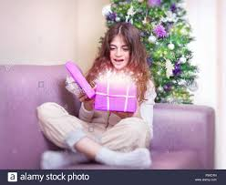 cheerful teen opening gift box with magic glowing present