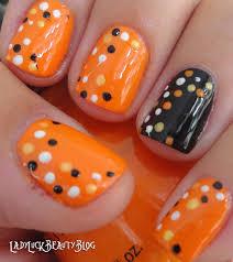 orange base nails with white black and yellow dots design nail art