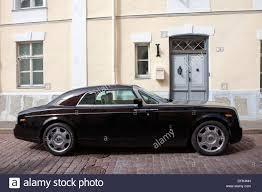roll royce side side view of a black rolls royce phantom parked on side of street