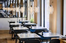 guests enjoy meal under modern restaurant pendant lighting in