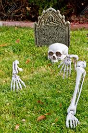 halloween skeleton bones and tombstone decorations in yard stock