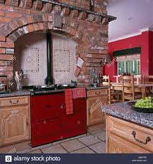 exposed brick wall above oven and hob in pale green fitted kitchen