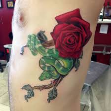 green ink snake with rose tattoo on man left side rib
