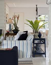beach house living room with stripes slipcover and houseplants