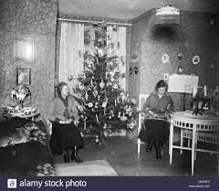 two women on christmas eve with a christmas tree in front of the