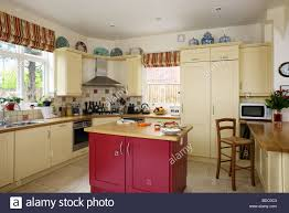 country kitchen with fitted cream units and red island unit and