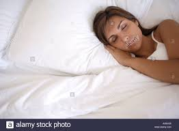 woman asleep in bed with white bed linen viewed from above stock
