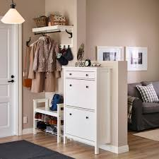 a small hallway with a white shoe cabinet and a seating bench with