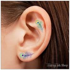 small peacock feather tattoo on finger photos pictures and