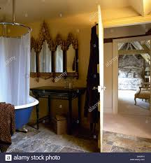 gothic style mirror above metal table in bathroom with shower