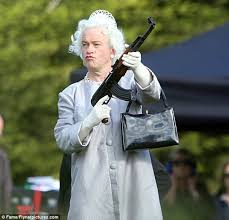 harry enfield becomes the queen toting around an automatic weapon