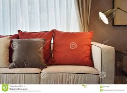 Pillows For Brown Sofa by Red And Brown Pillows On Beige Sofa With A Bras Lamp Stock Photo