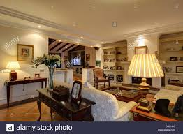 Table Behind Sofa by Lighted Lamps And Down Lighting In Comfortable Spanish Living Room