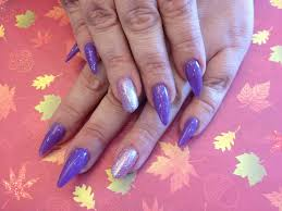 stiletto nails and edge nail on ring finger with purple gel polish